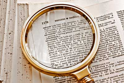 Our Story - Magnifier and dictionary picture of the word success